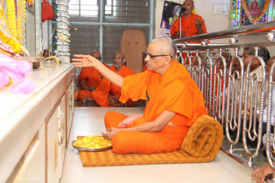 His Divine Holiness Acharya Swamishree showers fresh flower petals at the lotus feet of the Lord