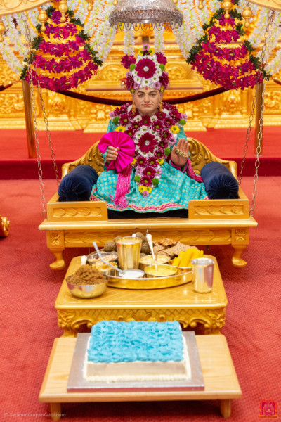 Divine darshan of Jeevanpran Shree Abji Bapashree seated on the charming golden swing dining on an evening dish and delicious cake