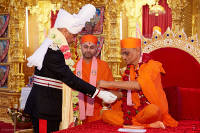 Acharya Swamishree Maharaj ties the sacred red thread around the wrist of Lord Lieutenant Sir Kenneth Olisa OBE, Her Majesty's representative for Greater London