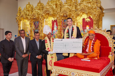 The cheque for £45,000 is presented by Acharya Swamishree Maharaj and Lord Lieutenant Sir Kenneth Olisa OBE to Save the Children
