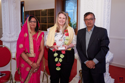 Disciples present a prasad shawl, a garland of flowers and prasad to the Save the Children representative
