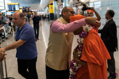 Disciples offer garlands of flowers to His Divine Holiness Acharya Swamishree at London's Heathrow Airport
