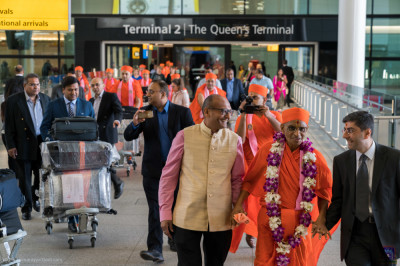 Disciples escort His Divine Holiness Acharya Swamishree out of the airport