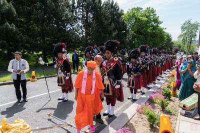 His Divine Holiness Acharya Swamishree boards the golden chariot as Shree Muktajeevan Swamibapa Pipe Band London perform
