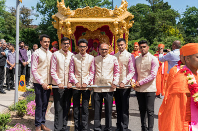Disciples pull the golden chariot into the mandir complex