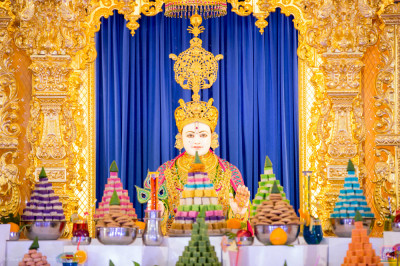 Divine darshan of Lord Shree Swaminarayan dining on the huge annakut of sweet items, savoury items, drinks and fruit