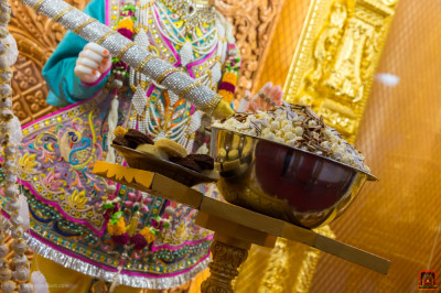 Divine darshan of Lord Shree Swaminarayan holding a large colour spray dining on pop corn and dates
