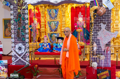 Divine darshan of His Divine Holiness Acharya Swamishree gently swinging the Lord seated on the swing