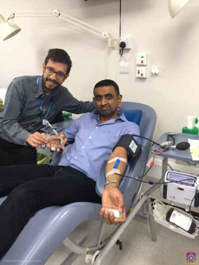Director of Blood Donation (NHSBT) Mike Stredder presents the award to Muks Rabadia