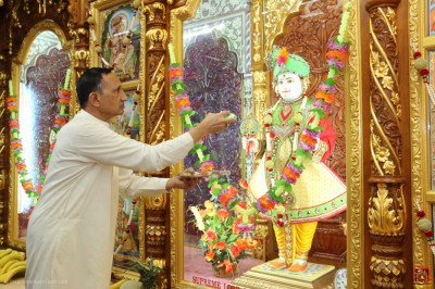 A disciple offers cake to Lord Shree Swaminarayan
