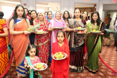 Disciples prepare to offer Lord Shree Swaminarayan various foods including fruits, dry nuts, and sweets