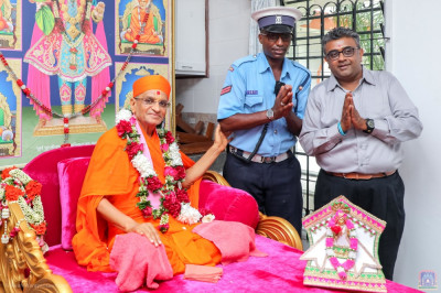 H.D.H Acharya Swamishree blesses a devotee and a police escort member