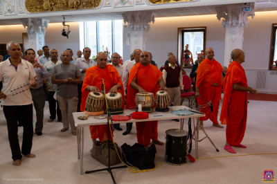 Sants and disciples perform percussion instruments during the dhoon