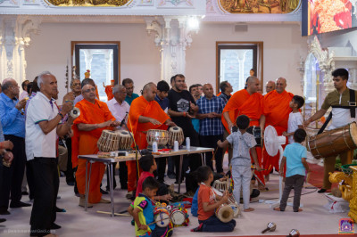 Sants and disciples perform on various percussion instruments accompanying the dhoon