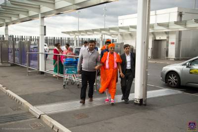Disciples escort His Divine Holiness Acharya Swamishree Maharaj into the airport terminal building