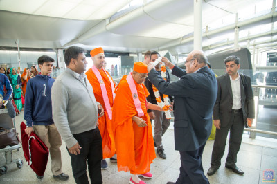 Disciples offer a garland of flowers to His Divine Holiness Acharya Swamishree Maharaj