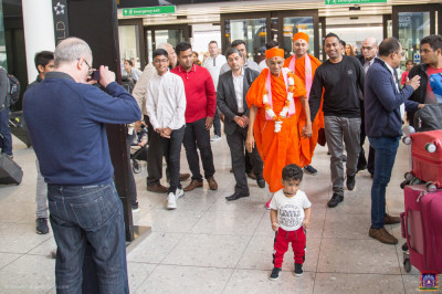 Disciples escort His Divine Holiness Acharya Swamishree Maharaj into the departures area