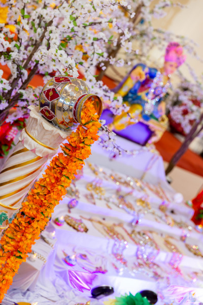 Divine darshan of the Lord with rangoli patterns and various golden jewelry