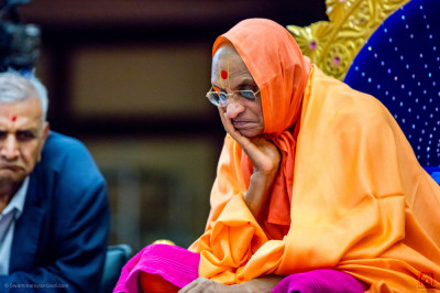 H.D.H Acharya Swamishree having a look at the Vachanamrut being recited by the devotees