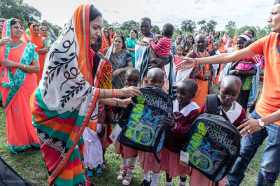 Devotees give school bags to the students