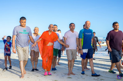 Devotees having a walk with H.D.H Acharya Swamishree on the beach