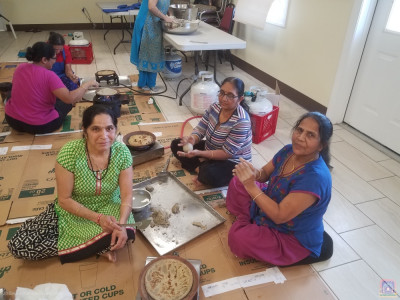 Disciples prepare bajra na rotla (millet flour bread). They mix and shape the dough by hand and then cook it on clay skillets.