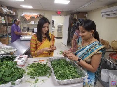 Disciples chop cilantro for the eggplant shak and khichdi.
