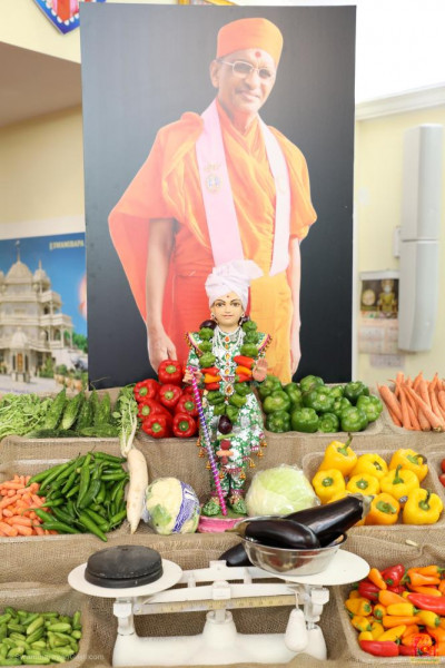 "Divine darshan of Lord Shree Swaminarayan and His Divine Holiness Acharya Swamishree as part of the ""shak-bhaaji market"" scene decorations."