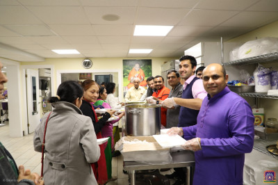 Disciples serve prasad to conclude the celebrations.
