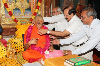 Disciples offer a garland of roses to His Divine Holiness Acharya Swamishree on the occasion of the anniversary of Shree Ishwar-sad vidyashram