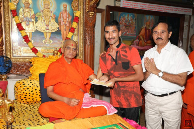 His Divine Holiness Acharya Swamishree presents a donation to the school