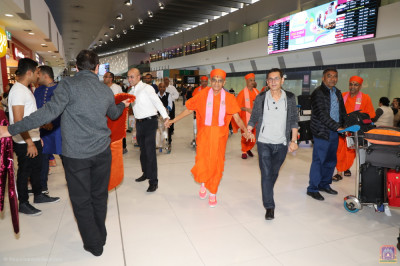 Disciples escort His Divine Holiness Acharya Swamishree at the airport