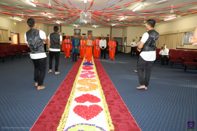 Disciples perform a devotional dance as His Divine Holiness Acharya Swamishree walks into the mandir on the flower petal walkway