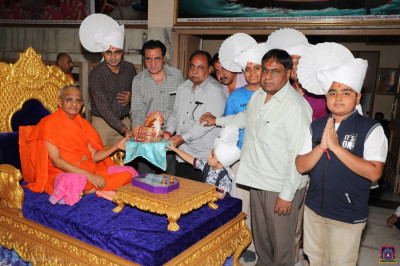 Disciples offer various dress items to Lord Shree Swaminarayan