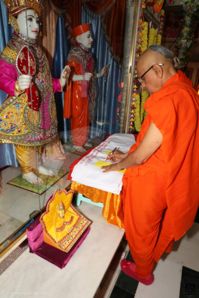 His Divine Holiness Acharya Swamishree inscribes the divine names of Lord Shree Swaminarayan on the new mandir flags