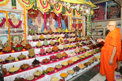 A grand annakut of sweet and savoury items is presented to Lord Shree Swaminarayanbapa Swamibapa as His Divine Holiness Acharya Swamishree performs aarti