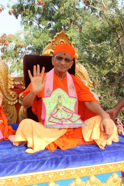 Acharya Swamishree Maharaj gives darshan seated on a chariot at the start of a procession in Bhensal, Panchmahal
