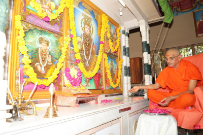 His Divine Holiness Acharya Swamishree showers rose petals at the lotus feet of the Lord as part of the anniversary poojan ceremony