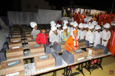 His Divine Holiness Acharya Swamishree unveils the sewing machines to be donated to poor local widows