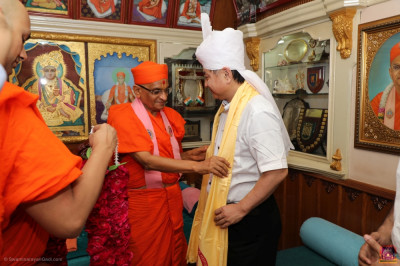 His Divine Holiness Acharya Swamishree presents a prasad shawl to Mr. Kodama