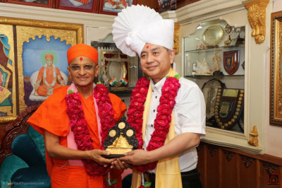 His Divine Holiness Acharya Swamishree presents a momento to Mr. Kodama