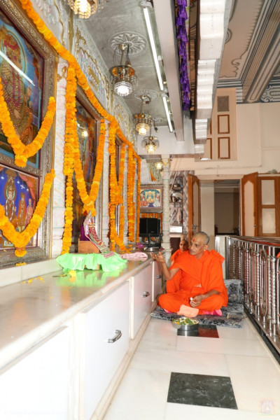 His Divine Holiness Acharya Swamishree showers fresh fragrant flower petals at the lotus feet of the Lord
