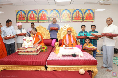 His Divine Holiness Acharya Swamishree blesses disciples offering gifts to the Lord