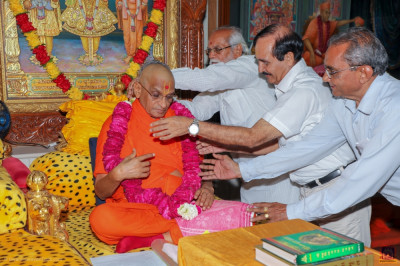 Disciples offer a garland of bright pink and red roses to His Divine Holiness Acharya Swamishree