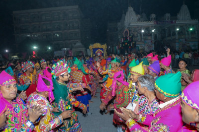 Disciples dressed in bright traditional authentic Indian dress perform various devotional dances during raas