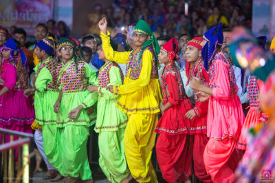 Disciples dressed in colourful traditional Indian dress perform devotional dances during raas