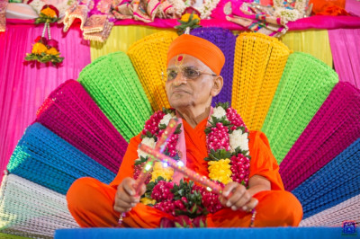Divine darshan of His Divine Holiness Acharya Swamishree holding dandia sparkling with coloured lights