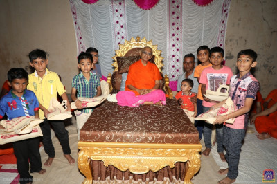His Divine Holiness Acharya Swamishree blesses young disciples and gifts them with stationary