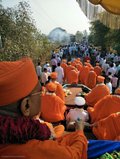 Acharya Swamishree Maharaj gives darshan during a procession in Malgun