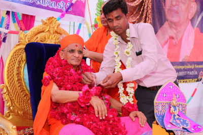 A disciple puts a large garland of roses on Acharya Swamishree Maharaj